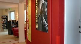 Rød udstillingsvæg med opslagstavle på toiletkerne